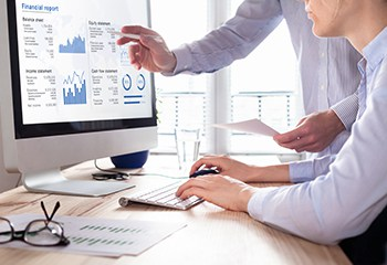 Team of consulting auditors auditing the financial report data of the company (balance sheet, income statement) on computer screen with business charts, fintech